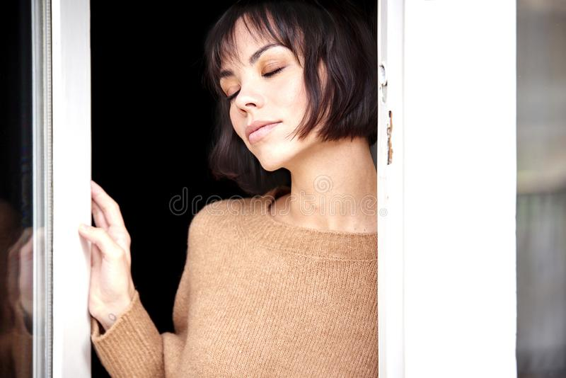 Beautiful young standing at window and daydreaming stock photography