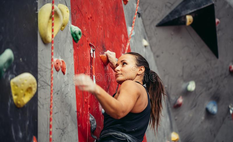 Beautiful young strong woman climbing on red artificial wall top view. royalty free stock images
