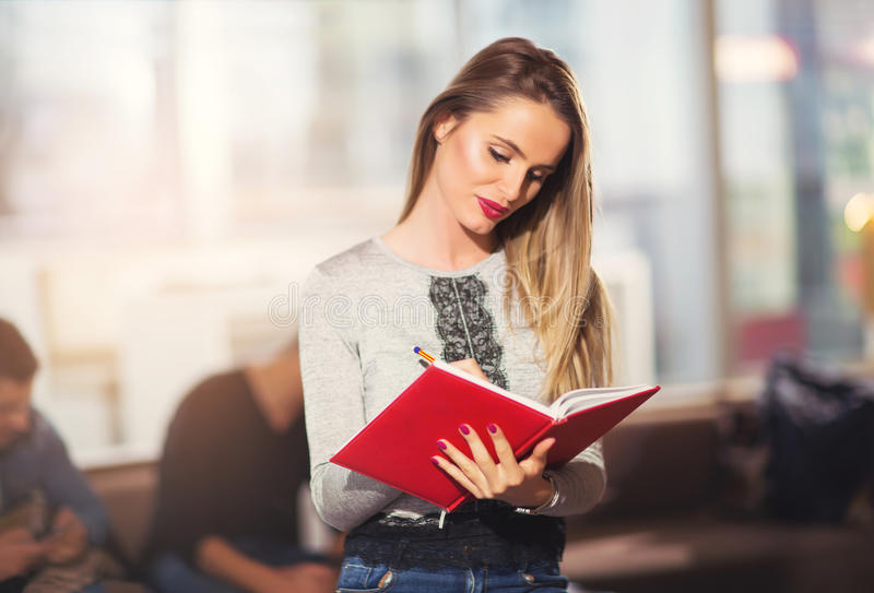 Beautiful young student with book. Studying or preparing for exams in a cafe stock image