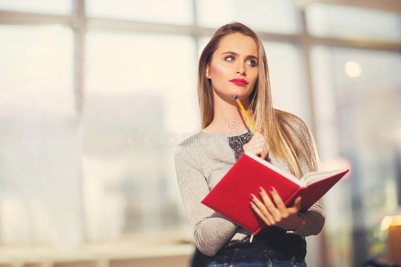 Beautiful young student with book. Studying or preparing for exams in a cafe royalty free stock photos