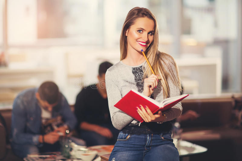Beautiful young student with book. Studying or preparing for exams in a cafe royalty free stock photo