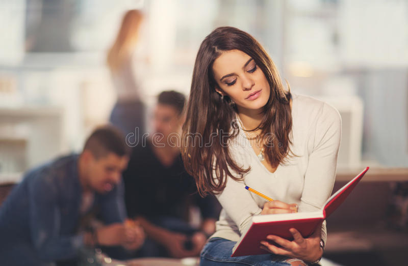 Beautiful young student with book. Studying or preparing for exams in a cafe stock photos