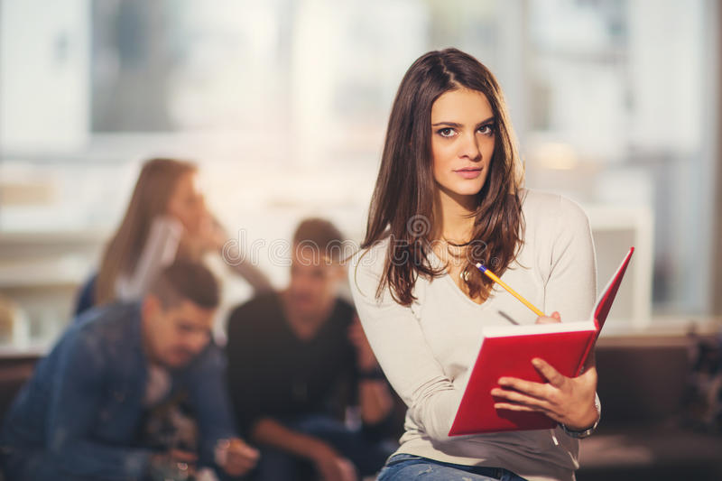 Beautiful young student with book. Studying or preparing for exams in a cafe royalty free stock images