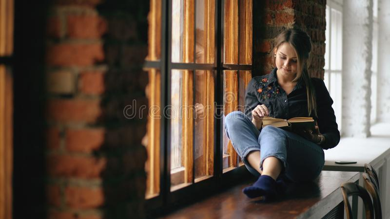 Beautiful young student girl reading book sit on windowsill in university classroom indoors royalty free stock photo