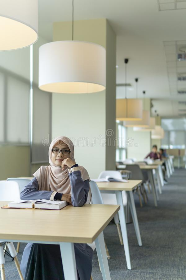 Beautiful young student in the library. A beautiful Muslimah student with glass sitting in the library and smiling royalty free stock photo