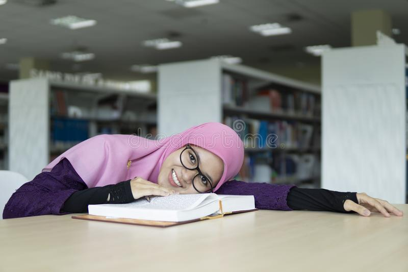 Beautiful young student in the library. A beautiful Muslimah student holding a pen, lying her head on the book and smiling royalty free stock image