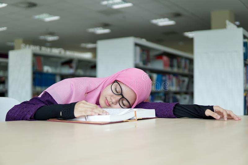 Beautiful young student in the library. A beautiful Muslimah student holding a pen and sleeping on the book in the library stock photo