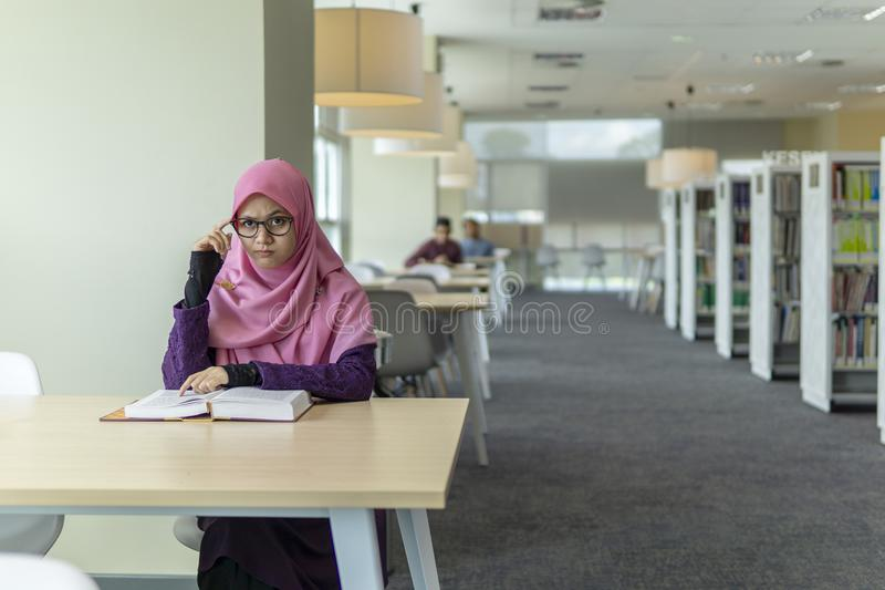 Beautiful young student in the library. A beautiful Muslimah student sitting in the library with book open on the table and thinking with facial expression stock photography