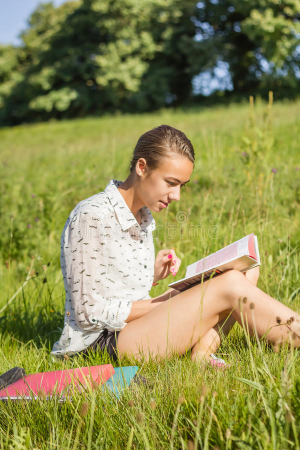Beautiful young student reading a book in the park royalty free stock photos