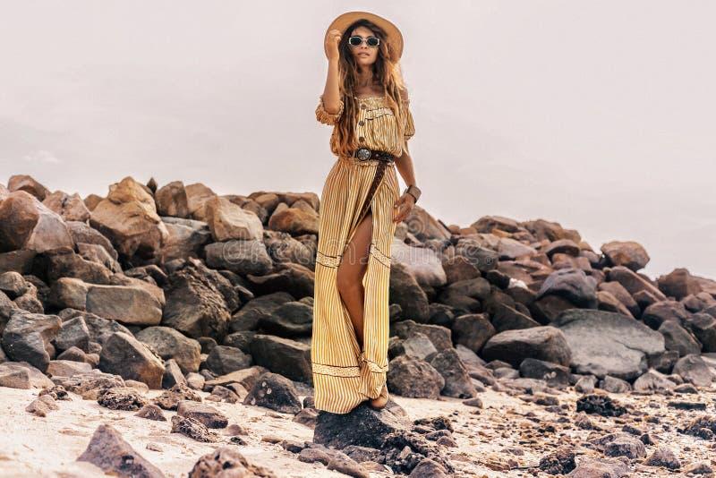 Beautiful young stylish boho woman in elegant dress outdoors wearing hat and sunglasses at sunset stock photo