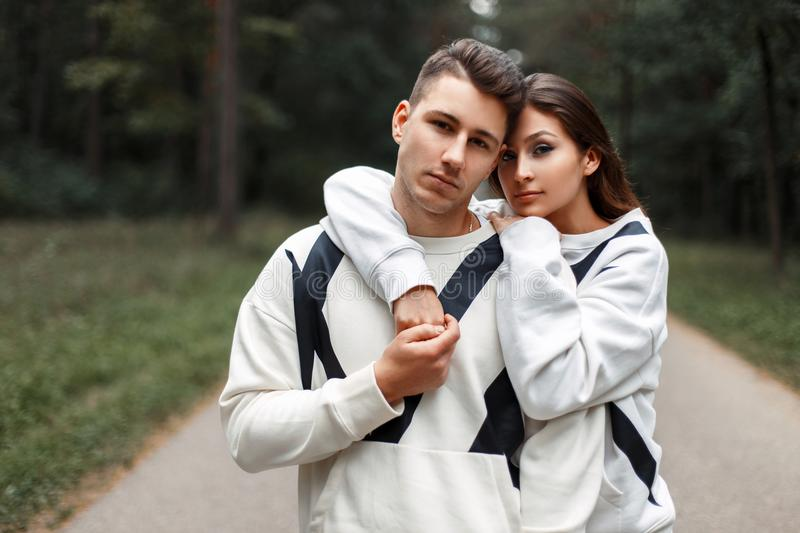 Beautiful young stylish couple in identical white sweaters. Hugging in the woods royalty free stock image