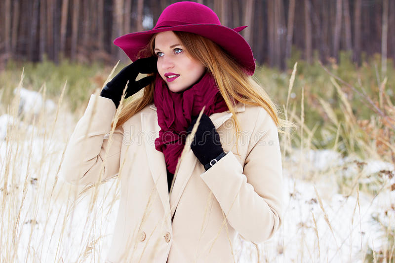 Beautiful, young and stylish girl in coat and hat straightens her hair. Fashion. royalty free stock photos