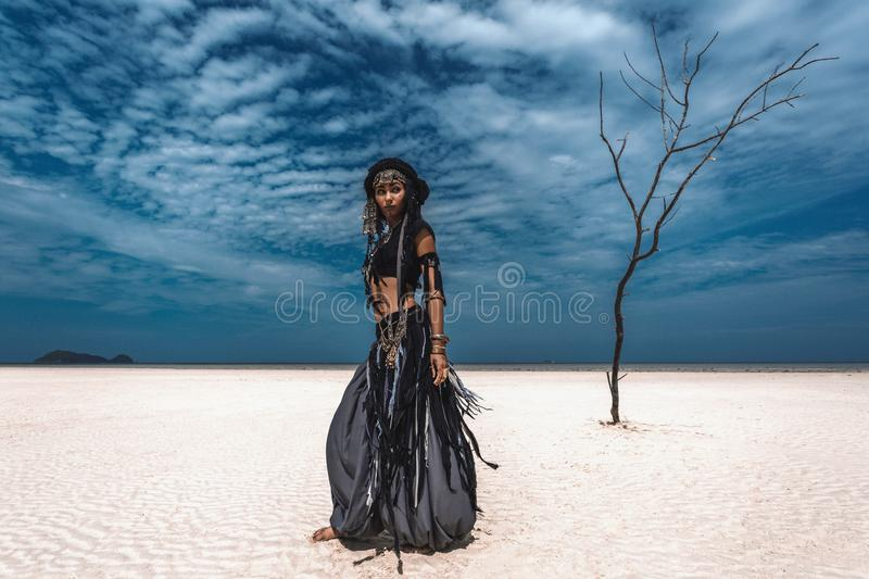 Beautiful young stylish tribal dancer. Woman in oriental costume in desert sands. Beautiful young stylish tribal dancer. Woman in oriental costume in desert royalty free stock images