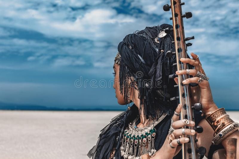 Beautiful young stylish tribal woman in oriental costume playing stock images
