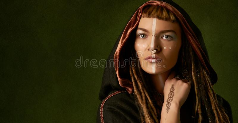 Beautiful, young, stylish woman with dreadlocks in a black, tribal costume on green background stock image