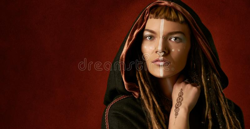 Beautiful, young, stylish woman with dreadlocks in a black, tribal costume on red background royalty free stock photo
