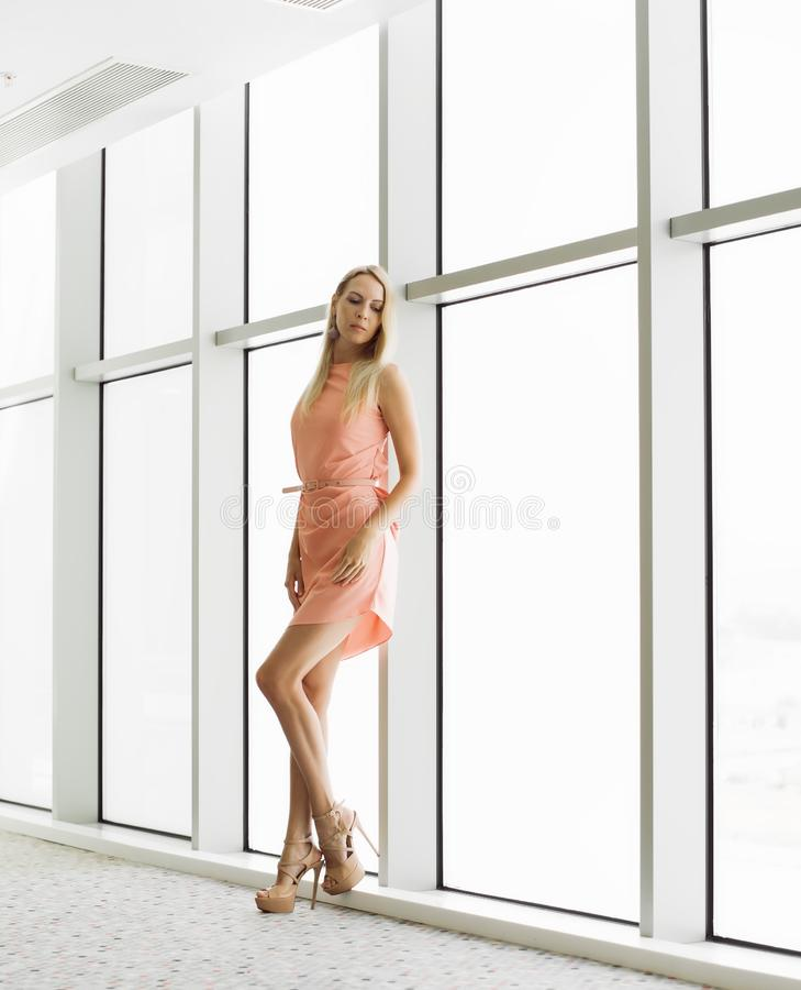 Stylish woman near window in the office building royalty free stock photography