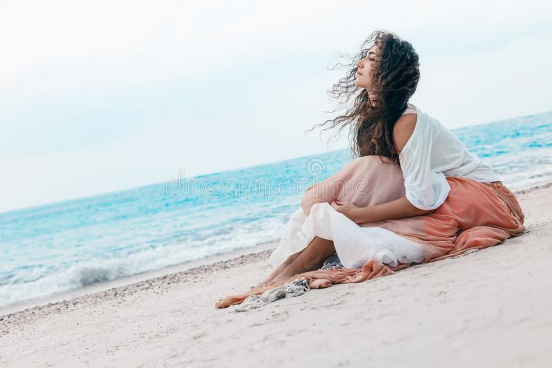 Beautiful young stylish woman in pink skirt on the beach royalty free stock image