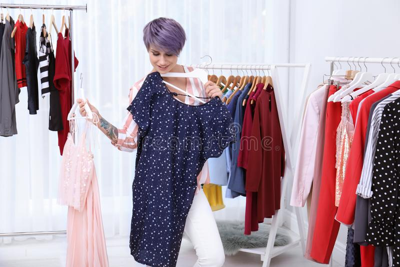 Beautiful young stylist choosing clothes royalty free stock images