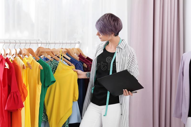 Beautiful young stylist with clipboard choosing clothes stock photos
