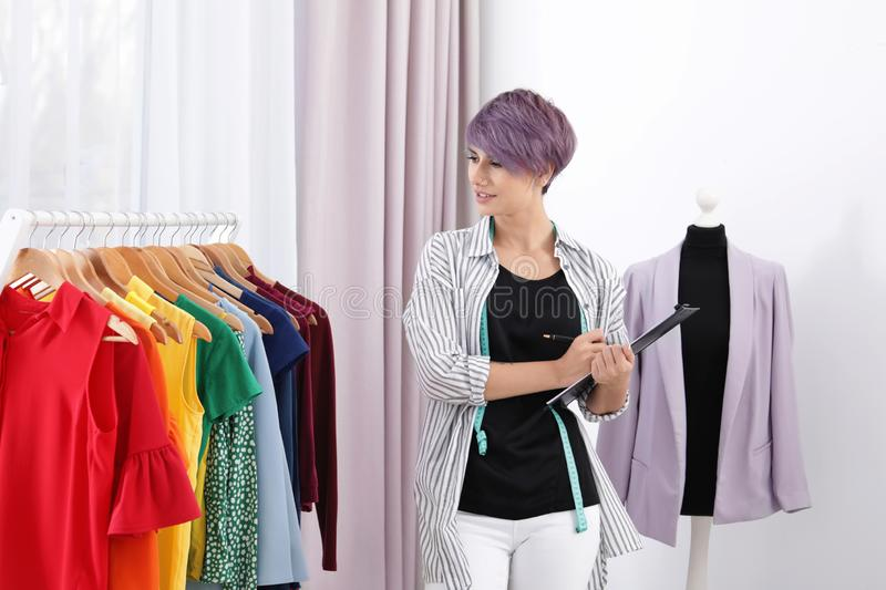Beautiful young stylist holding clipboard near rack with designer clothes stock image