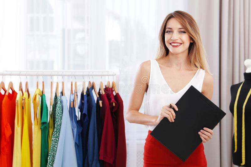 Beautiful young stylist holding clipboard near rack with designer clothes royalty free stock photo