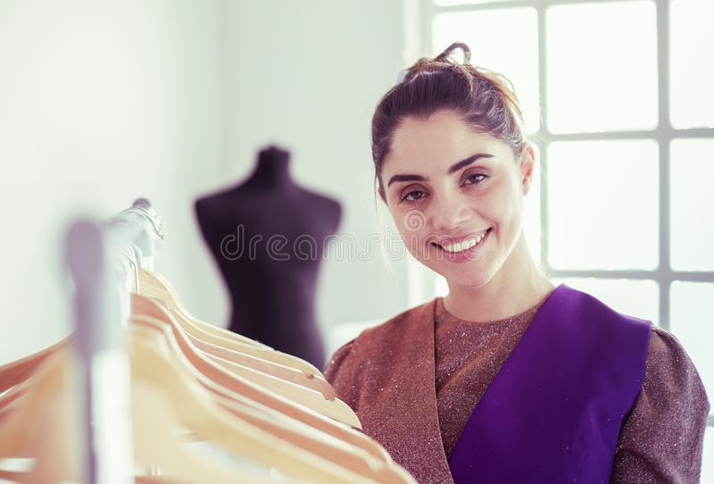 Beautiful young stylist near rack with hangers stock image