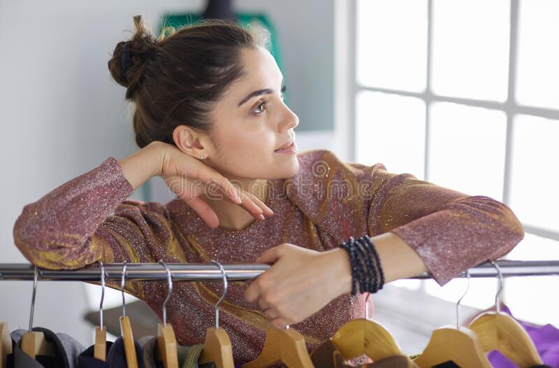 Beautiful young stylist near rack with hangers royalty free stock photography