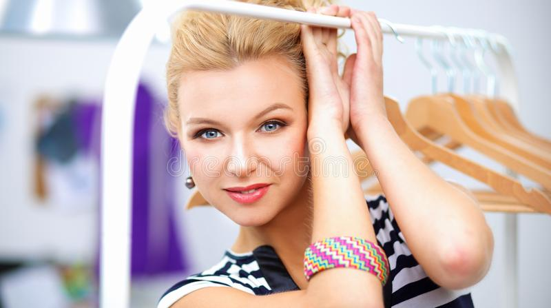 Beautiful young stylist near rack with hangers in office stock images
