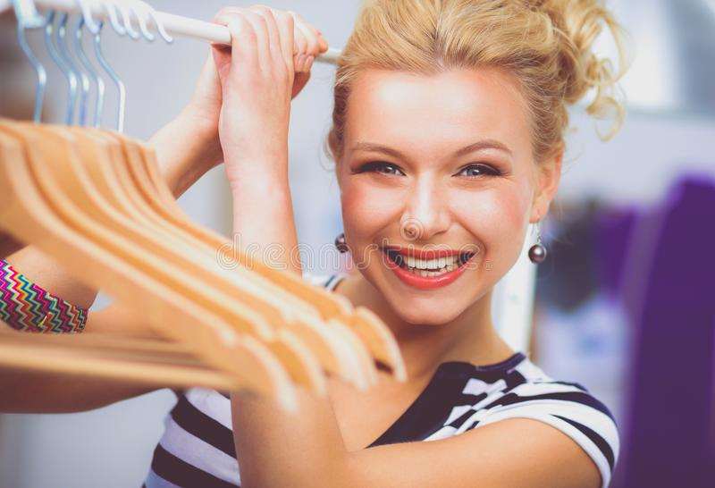 Beautiful young stylist near rack with hangers in office stock photo