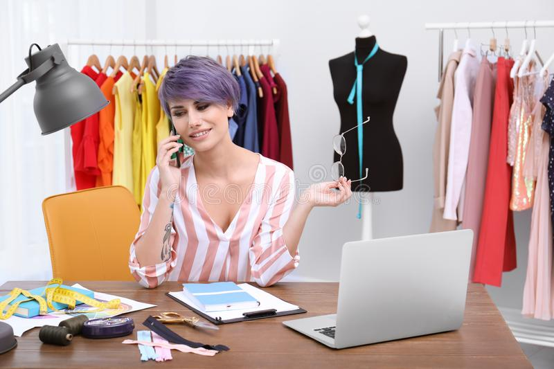 Beautiful young stylist talking on phone at workplace near rack royalty free stock photos