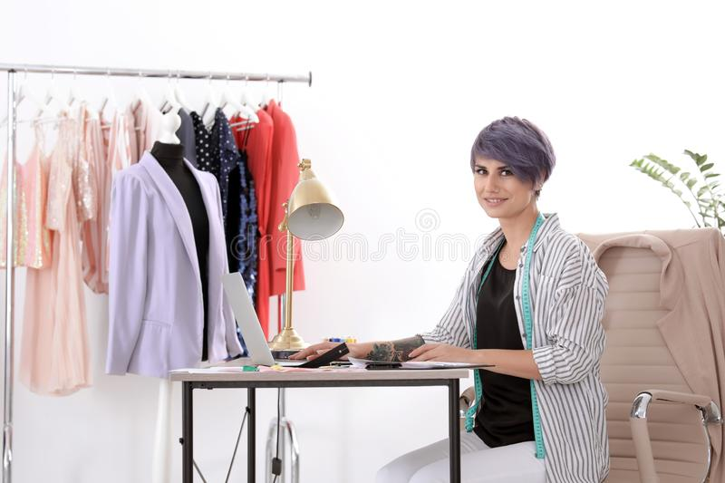 Beautiful young stylist working with laptop in studio. royalty free stock photos