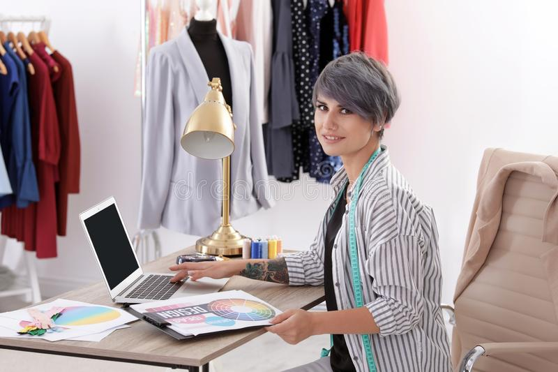 Beautiful young stylist working with laptop in studio royalty free stock photo
