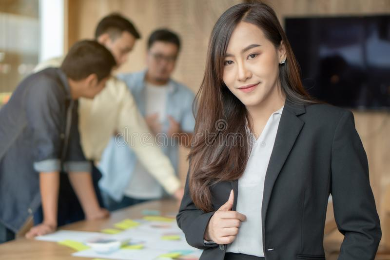 Beautiful young successful business woman standing in meeting room,Her feel feeling confidence and determination with other worker royalty free stock photos