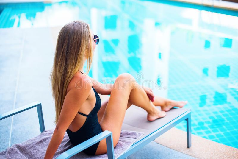 Beautiful Young Suntanned Female Long Hair. On Plank Bed near Swimming Pool Resort Suntan Skin Holiday Vacation stock photo