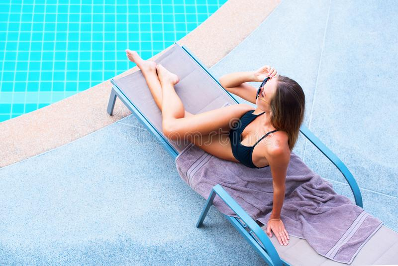 Beautiful Young Suntanned Female Long Hair. On Plank Bed near Swimming Pool Resort Suntan Skin Holiday Vacation stock photography