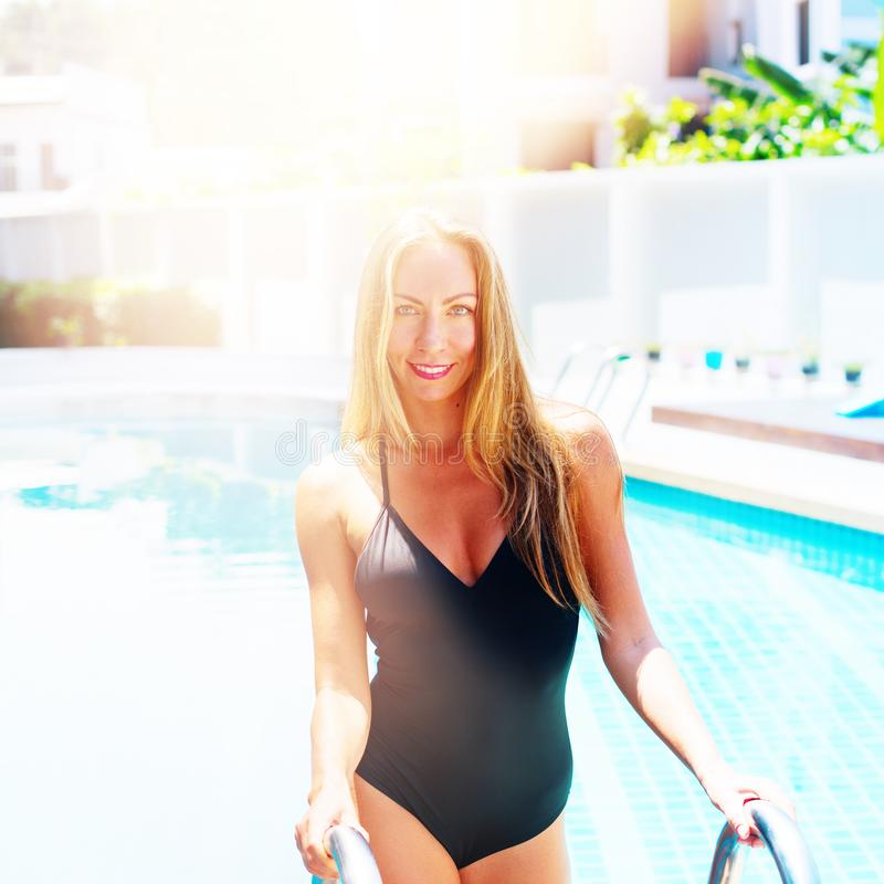Beautiful Young Suntanned Woman Blonde Vacation. Portrait Beautiful Young Suntanned Woman Blonde Long Hair Bathing Suit Black Swimming Pool Resort Suntan Skin stock image