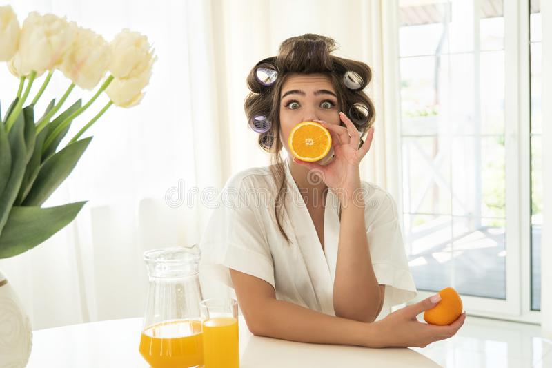 Beautiful young surprised brunette woman in hair curlers holding one orange near her mouth and another in her hand in stock photos