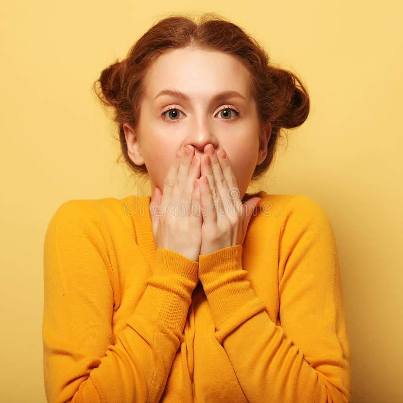 Beautiful young surprised redhair woman over yellow background royalty free stock image