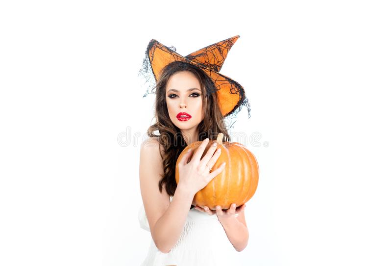 Beautiful young surprised woman in witch hat and Halloween costume holding pumpkin - isolated on white background stock photo