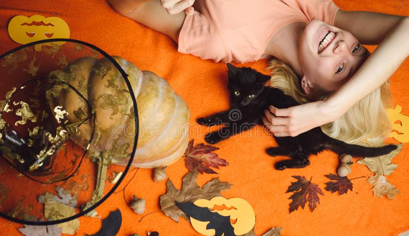 Beautiful young surprised woman in witches hat and costume holding pumpkin. Black cat with pretty girl. Beautiful young royalty free stock photos