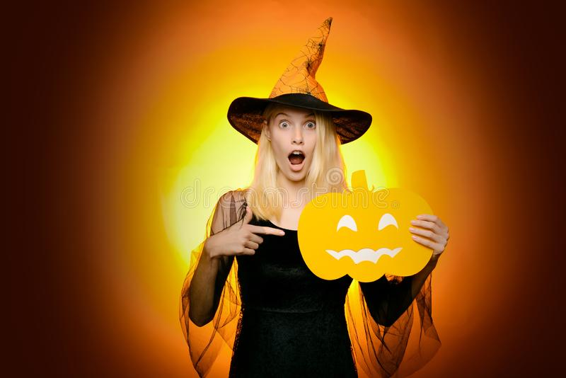 Beautiful young surprised woman in witches hat and costume pointing hand - showing products. Halloween Woman portrait stock image