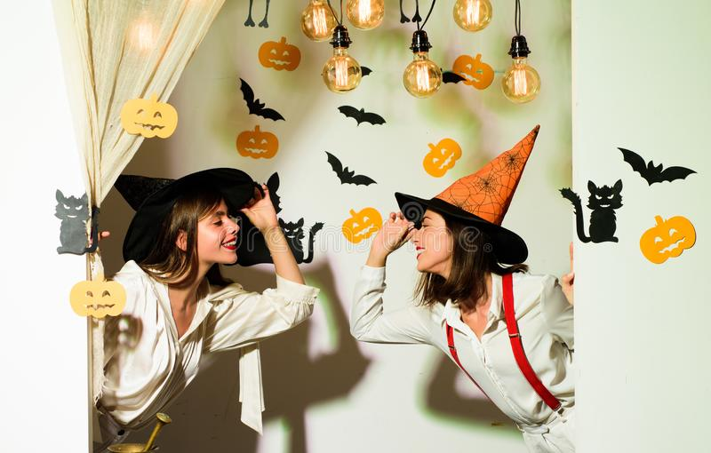 Beautiful young surprised woman in witches hat and costume pointing hand - showing products. stock images
