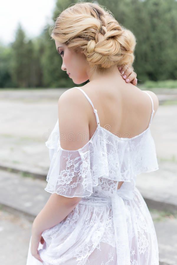 Beautiful young sweet blonde girl with wedding bouquet in the hands of the boudoir in a white dress with evening hairstyle walks. Beautiful young sweet blonde royalty free stock photo