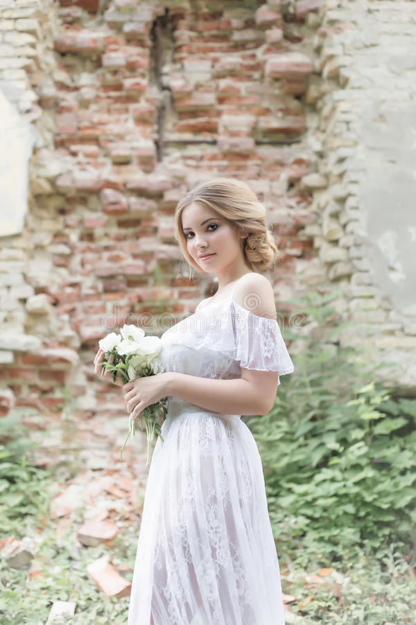 Beautiful young sweet blonde girl with wedding bouquet in the hands of the boudoir in a white dress with evening hairstyle walks. Beautiful young sweet blonde stock photography
