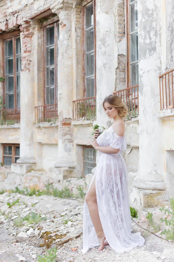 Beautiful young sweet blonde girl with wedding bouquet in the hands of the boudoir in a white dress with evening hairstyle walks. Beautiful young sweet blonde royalty free stock photos