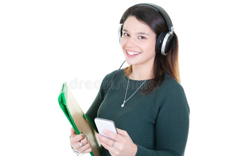 Beautiful young teenage girl in headphones listening to music with coffee tea mug cup standing on white background royalty free stock images