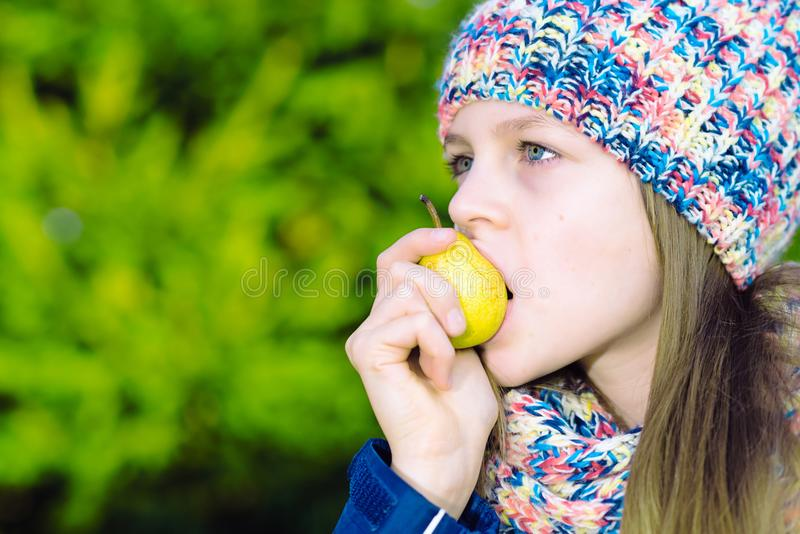 Beautiful young teenager girl bites a pear stock image