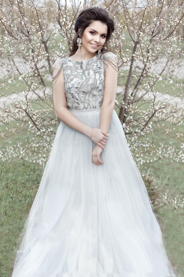 Beautiful young tender gay girl with a beautiful wedding hairstyle with a snow-white smile in a light dress is walking in a spring royalty free stock photography