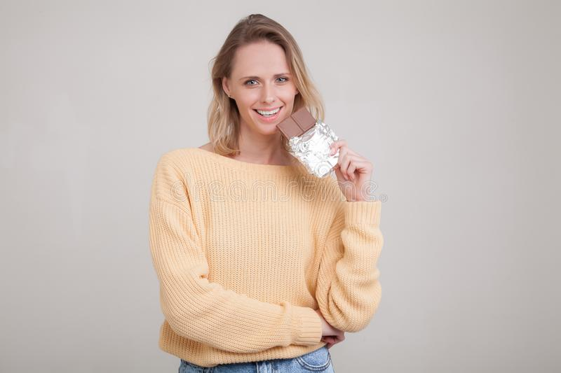 A beautiful young tender girl with blond hair holds a chocolate bar in the face she is wearing in a yellow sweater. poses against stock photography